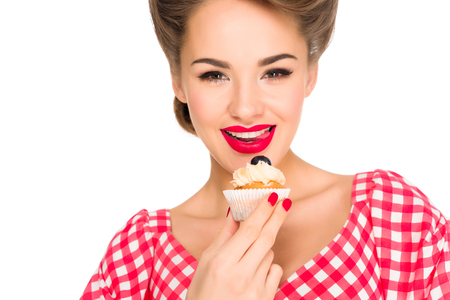 portrait of beautiful woman in pin up clothing with cupcake isolated on white