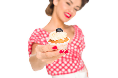 selective focus of woman in pin up clothing showing cupcake isolated on white 写真素材