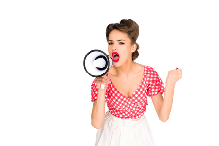 portrait of fashionable young woman in pin up style clothing screaming into loudspeaker isolated on white