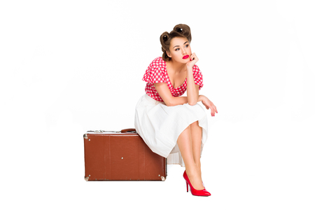 bored beautiful woman in retro clothing sitting on suitcase isolated on white