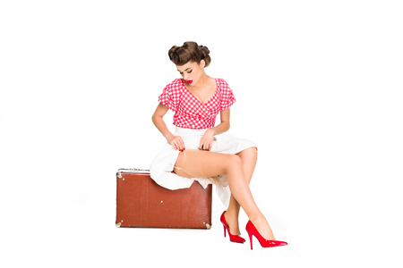 beautiful young woman in retro clothing sitting on suitcase isolated on white