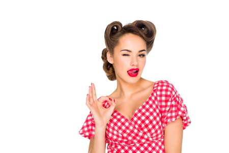 beautiful woman in retro clothing sticking tongue out and showing ok sign isolated on white