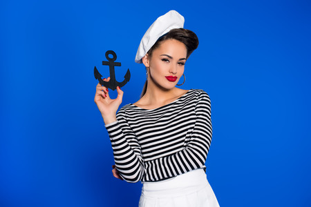 portrait of fashionable young woman in retro clothing with anchor in hand isolated on blue Imagens
