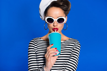 portrait of stylish young woman with beverage in paper cup isolated on blue Stockfoto