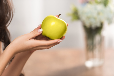 close-up partial view of girl holding fresh green apple