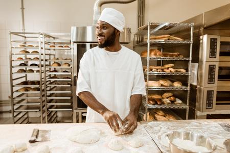 african american baker preparing raw dough for pastry on baking manufacture 版權商用圖片