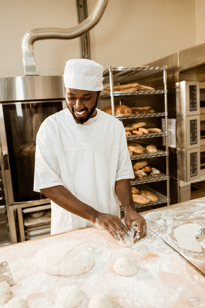 smiling african american baker preparing raw dough for pastry on baking manufacture