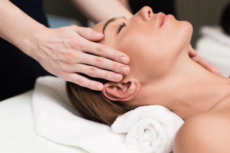 young woman relaxing and having head massage in spa salon Stock Photo