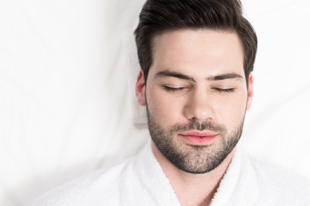 close-up view of handsome bearded man in bathrobe relaxing in spa salon