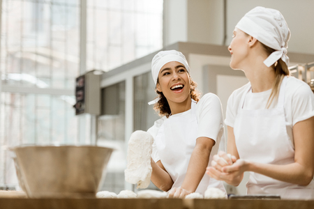 laughing female bakers kneading dough together at baking manufacture Stock Photo