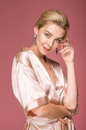 attractive blonde woman posing in earrings and silk robe, isolated on pink