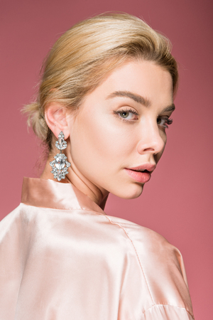 attractive blonde woman posing in earrings and silk robe, isolated on pink Archivio Fotografico