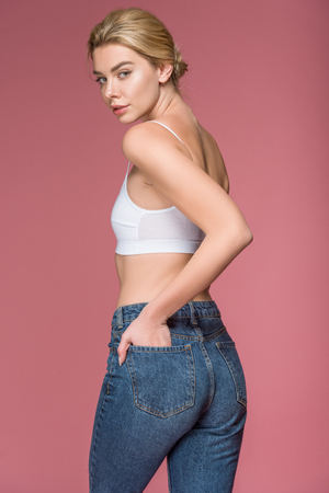 attractive blonde woman posing in jeans and white bra, isolated on pink