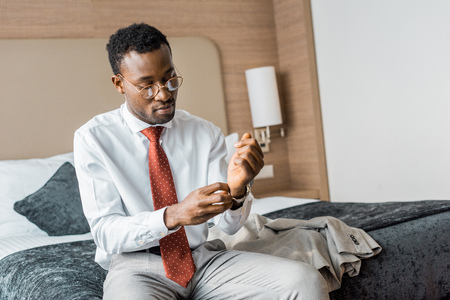 young african american businessman wearing wristwatch while sitting on bed in hotel room Stock Photo