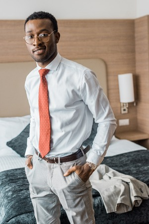 smiling businessman in red tie standing in hotel room Stock Photo