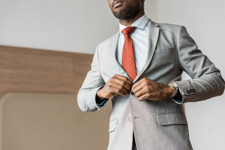 cropped view of african american businessman buttoning gray jacket Stock Photo