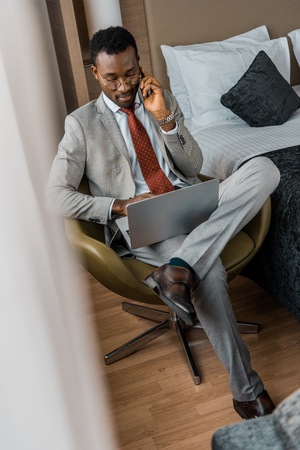 handsome african american businessman talking on smartphone and using laptop in hotel room
