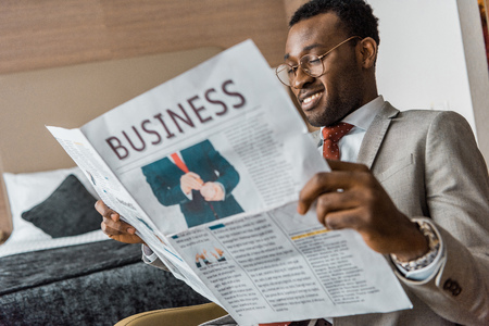 smiling african american businessman in suit reading business newspaper in hotel room 스톡 콘텐츠