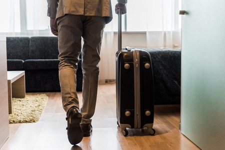 cropped view of businessman in suit with baggage coming into hotel room Stock Photo