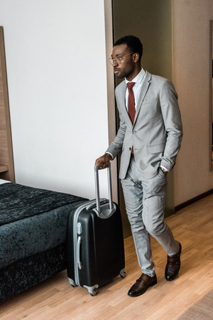 african american businessman with travel bag coming into hotel room Фото со стока