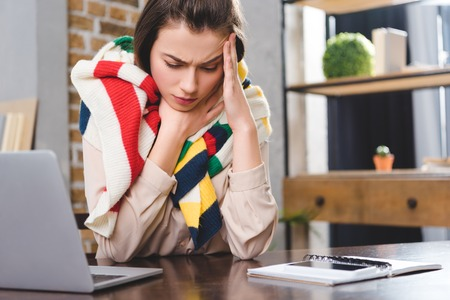 sick young businesswoman in scarf suffering from headache at workplace