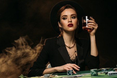 attractive girl in jacket and hat holding glass of whiskey at poker table in casino and looking away 版權商用圖片