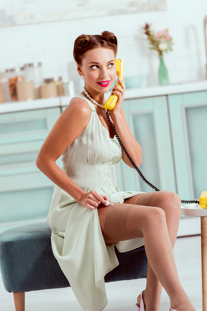 Beautiful pin up girl sitting on ottoman and talking on vintage yellow phone Stockfoto