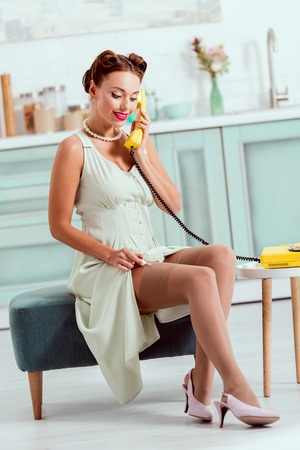 Attractive pin up girl talking on vintage yellow phone while sitting on ottoman
