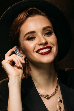 happy attractive girl in jacket and hat holding poker chips and looking at camera