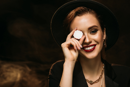 happy attractive girl in jacket and hat covering eye with poker chip and looking at camera Stock Photo