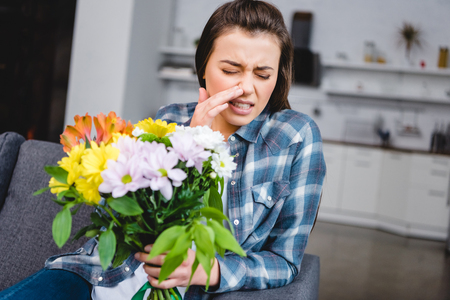 young woman with allergy sneezing and holding bouquet of flowers Stock Photo