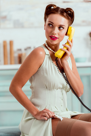 attractive pin up girl talking on vintage yellow phone while fixing stockings