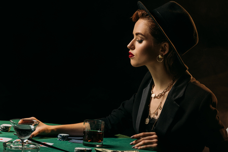 side view of attractive girl in jacket and hat sitting at poker table in casino Stock Photo