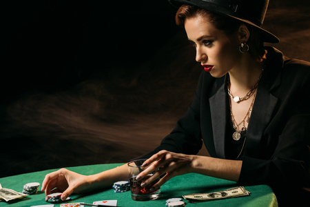 side view of attractive woman in jacket and hat holding glass of whiskey at poker table in casino