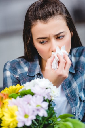 young woman with allergy holding facial tissue and looking at flowers