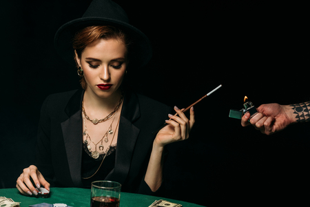 tattooed man lighting cigarette to attractive girl in jacket and hat at casino
