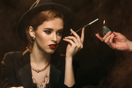 man lighting cigarette to attractive girl in jacket and hat on black
