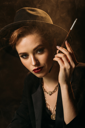 attractive girl in jacket and hat smoking cigarette on black and looking at camera
