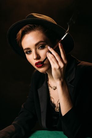 attractive girl in jacket and hat smoking cigarette at table isolated on black and looking at camera Фото со стока