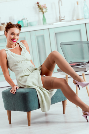 Smiling pin up girl sitting on ottoman near recor player Stockfoto