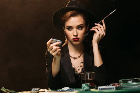 attractive girl in jacket and hat smoking cigarette at poker table in casino and looking away