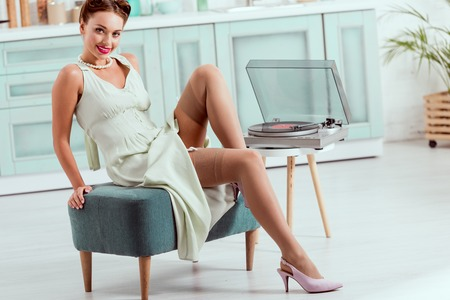 Flirty pin up girl sitting on ottoman near record player