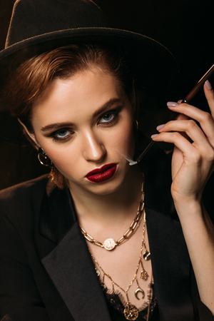 portrait of attractive girl in jacket and hat smoking cigarette on black and looking at camera
