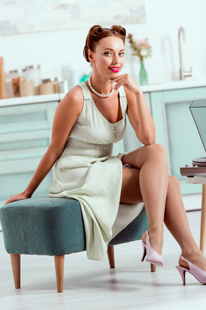 Beautiful pin up girl sitting on ottoman and looking at camera