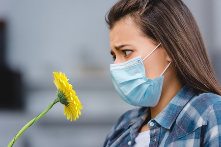 side view of young woman with allergy wearing medical mask and looking at flower