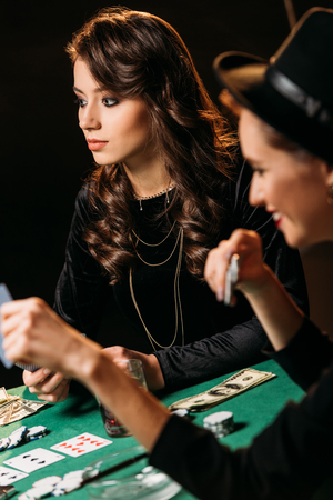 beautiful women playing poker with cards and chips at table in casino Stock Photo