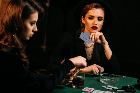 attractive girls playing poker together at table in casino Stock Photo