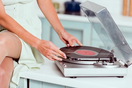 cropped view of pin up girl sitting on table with crossed legs and putting vinyl record on record player Stock Photo