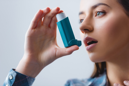 close-up view of young woman with asthma using inhaler