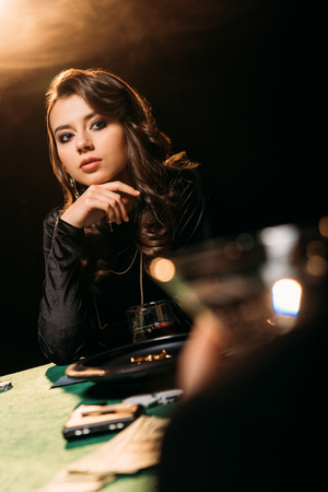 attractive pensive girl looking away at poker table in casino Stock Photo
